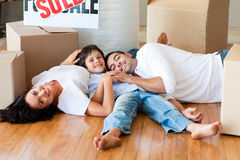 Family in a new house lying on floor with boxes Royalty Free Stock Image