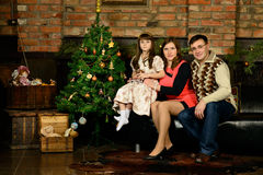 Family new year's eve around the Christmas tree Royalty Free Stock Images