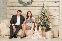 Family new year's eve around the Christmas tree Stock Photo