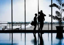 Family in a nice moment at Airport waiting for departure. Silhouette of a family in a nice moment at Airport waiting for departure Royalty Free Stock Photo