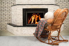 Family night.Two Teddy bear sitting on a rocking chair ,cuddling and watching the flames of the fire in the fireplace. Two Teddy bear sitting on a rocking chair stock photography