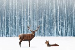 Family of noble deer in a snowy winter forest. Christmas fantasy image in blue and white color. Snowing