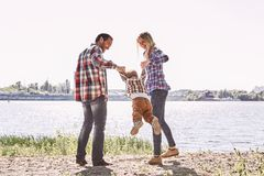 Family is not an important thing. It`s everything. Parents standing with their kid, holding his hands and lifting him up royalty free stock images