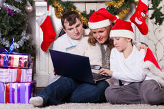 Family with notebook near Christmas tree. Stock Photos