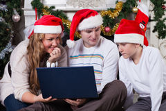 Family with notebook near Christmas tree. Royalty Free Stock Images