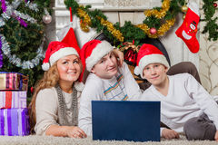 Family with notebook near Christmas tree. Royalty Free Stock Photography