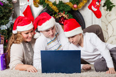 Family with notebook near Christmas tree. Stock Photo