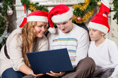 Family with notebook near Christmas tree. Stock Image