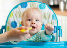 Family and nutrition concept - mother spoon feeding little baby sitting in highchair at home stock images