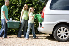 Family Of Three Loading Recycling Into Car, Side View Stock Images