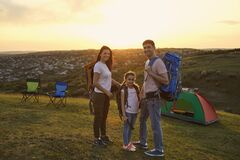 Free Family On A Camping In Nature. Portrait Of Happy Family With Backpacks Standing Near Their Tent On Mountain At Sunset. Stock Photography - 187024012