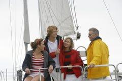 Family On Sailboat In Sea Stock Photo