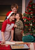 Family with one kid at christmas. Young boy kissing mum on cheek for baking christmas cake, dad watching, smiling Royalty Free Stock Image