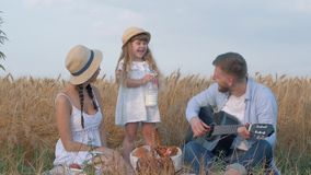 Family open air entertainment, young couple laughs at milk whiskers of their daughter when handsome man plays string. Family entertainment, young couple laughs stock video