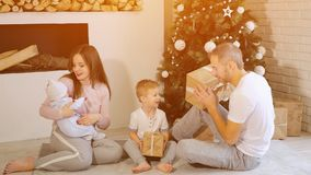Family opening Christmas gifts near tree stock images