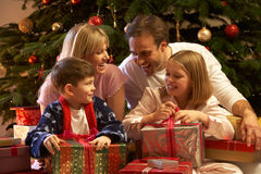 Family Opening Christmas Present In Front Of Tree. Smiling stock photography
