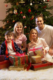 Family Opening Christmas Presents. Family Opening Christmas Present In Front Of Tree Smiling Stock Photos