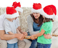 Family opening crackers together on the sofa Stock Photos