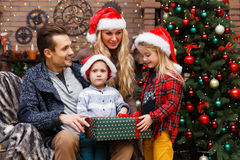 Family opening gifts at tree royalty free stock photography