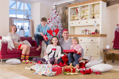 Family opening presents at Christmas Time. Two generation family in front of a christmas tree opening presents. They are all dressed for christmas and smiling at Stock Photos