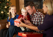 Family Opening Presents In Front Of Christmas Tree Stock Photos