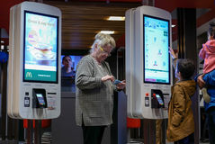 Family ordering food at self check out machine and old lady playing cellphone. At Mcdonalds restaurant Royalty Free Stock Photography