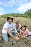 Family of organic farmers planting seedling Stock Photos