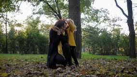 Family outdoor games, happy smiling female child having fun with charming young mother throw leaves on a walk in the