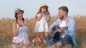 Family outdoor holidays, young daddy plays guitar while his wife claps hands and their little daughter in straw hat and