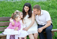 Family on outdoor, pregnant woman with child and man, city park, summer season, green grass and trees Stock Photos