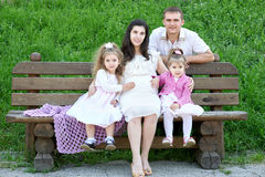 Family on outdoor, pregnant woman with child and man, city park, summer season, green grass and trees Stock Images