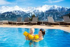 Family in outdoor swimming pool of alpine spa resort. Mother and baby play in outdoor swimming pool of luxury spa alpine resort in Alps mountains, Austria royalty free stock photo