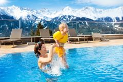 Family in outdoor swimming pool of alpine spa resort Stock Photo