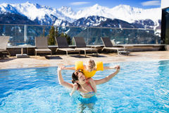 Family in outdoor swimming pool of alpine spa resort. Mother and baby play in outdoor swimming pool of luxury spa alpine resort in Alps mountains, Austria stock image