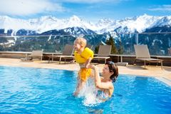 Family in outdoor swimming pool of alpine spa resort Royalty Free Stock Photos