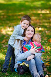 Family outdoors. Happy mother and two kids spending time outdoors at sunny autumn day royalty free stock photo