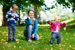 Family outdoors. Happy mother and two kids spending time outdoors at sunny autumn day stock photos