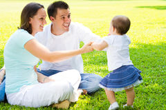 Family outdoors. Young happy family playing outdoors on green grass royalty free stock image