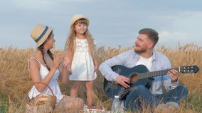 Family outdoors amusement, young man plays guitar while his woman and little cute daughter in straw hats and white stock video