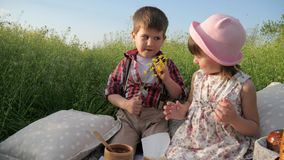 Family outdoors, boy with fields flowers in hand is looking at beautiful girl, two adorable children, boy is looking at. Beautiful girl, looking at each other stock video