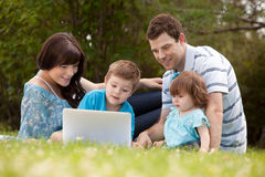 Family Outdoors with Computer. Happy family together outdoors with computer royalty free stock photo
