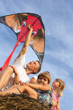 The family outdoors flying kite in the sky Stock Image