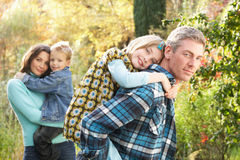Family Outdoors Giving Children piggyback. Family Group Outdoors In Autumn Landscape With Parents Giving Chiildren Piggyback royalty free stock photo