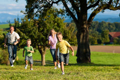 Family outdoors is running on a meadow. Happy family outdoors is running on a meadow on a beautiful summer day - they try to catch each other stock photo