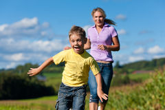 Family outdoors is running on a meadow. Happy family outdoors is running on a meadow on a beautiful summer day - the mother is trying to catch her son royalty free stock photography