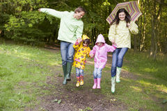 Family outdoors skipping with umbrella smiling