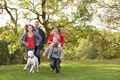 Family Outdoors Walking Through Park. Young Family Outdoors Walking Through Park With Dog Royalty Free Stock Photo