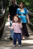 Family Outdoors on a Wooden Foot Bridge (2). A young couple with their two-year-old daughter leading the way on a wooden foot bridge outdoors.  The mother is Royalty Free Stock Photos