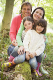 Family outdoors in woods sitting on log smiling Royalty Free Stock Photos