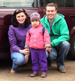 Family in outerwear in front of car Royalty Free Stock Photo